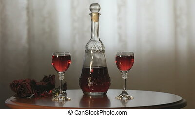 Two hands clink glasses with a liquor of red color - Two...