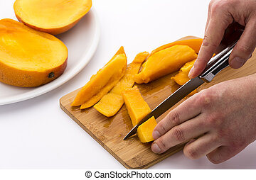 Two Hands Dicing A Mango Wedge With A First Cut - Two male...