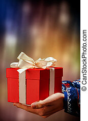 two hands hold a red present with white ribbon before coloured background