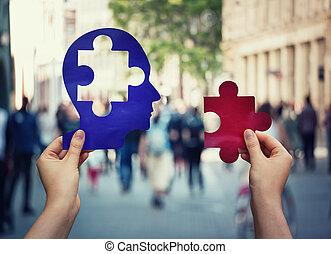 Two hands holding a paper with human head and a puzzle...