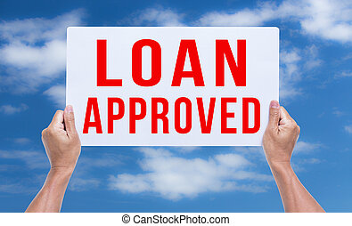Two hands holding brown cardboard with loan approved on blue sky background