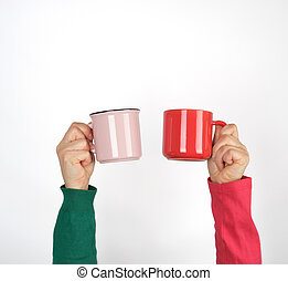 two hands holding ceramic mugs on a white background