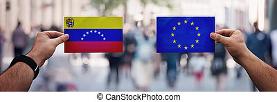 Two hands holding different flags, EU vs Venezuela on politics arena over crowded street background