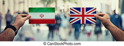 Two hands holding different flags, UK vs Iran on politics arena over crowded street background