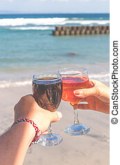 Two hands holding glasses with wine on sea background. Female and male hands with wine glasses.