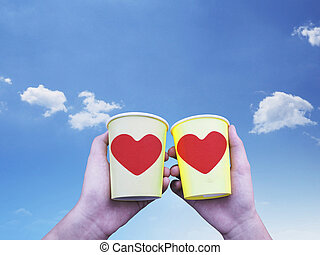 Two hands holding yellow paper cups of coffee with red heart shape