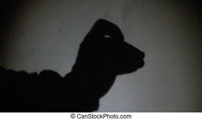 Two hands make a silhouette shadow show of a camel head against white background
