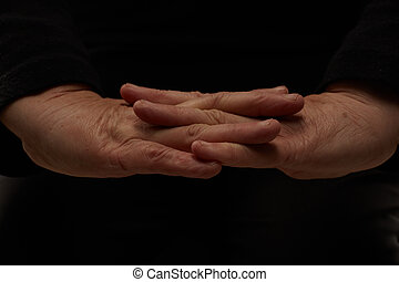 Two hands of an elderly woman. Close up on black background