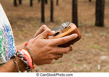 Two hands of man holding traditional African musical instrument kalimba in a forest.