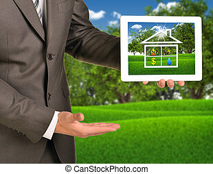 Two hands using tablet pc with picture of house icon