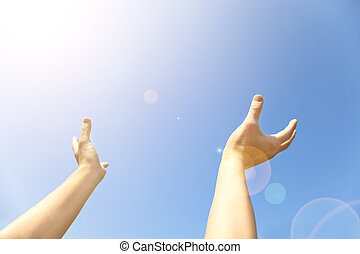 Two hands with the opened palms last upwards to the blue sky