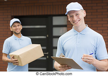 Two handsome couriers in blue uniforms standing in front of a house and waiting with delivery