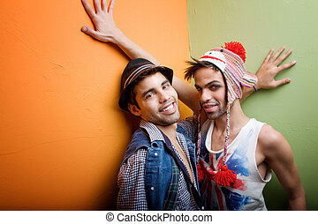 Two handsome gay young men standing in a corner