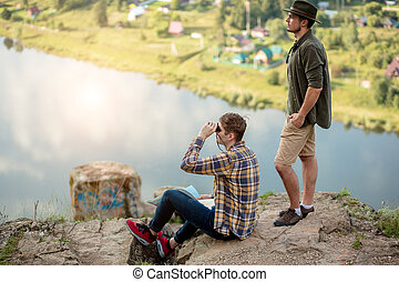 two handsome tourists having a rest on the top of rock