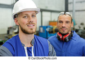 two handsome young men working in a factory