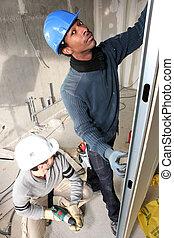 Two handymen fitting plasterboard