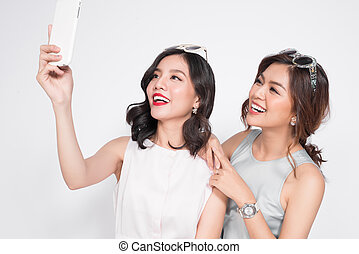 Two happy asian young women with smartphone taking selfie