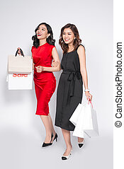Two happy attractive young women with shopping bags on white background