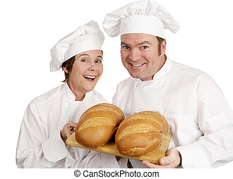 Two Happy Bakers - A male and female chef holding loaves of...