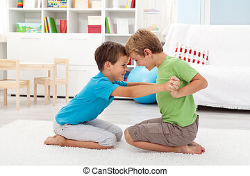 Two happy boys wrestling in the kids room