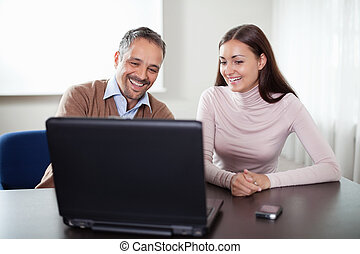 Two happy business colleagues working on laptop