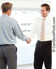 Two happy businessmen concluding a deal by shaking their hands