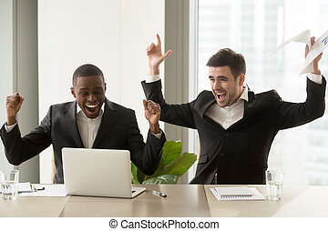 Two happy businessmen raising hands near laptop, celebrating...