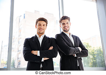 Two happy businessmen standing with arms crossed in office