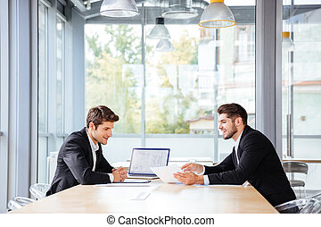 Two happy businessmen working together using laptop on business meeting