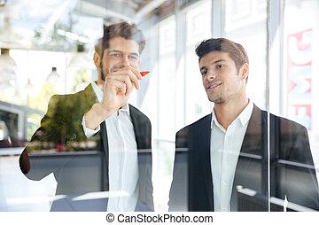 Two happy businessmen writing on glass board in office