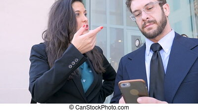 """Two happy businesspeople looking at mobile phone, shaking hands and leaving"""