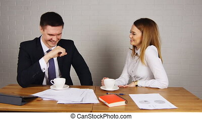 Two happy businesspeople with coffee at office talking