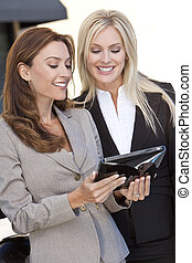 Two Happy Businesswomen Using a Tablet Computer