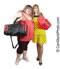 Two happy casual girls with travelling bags over white background