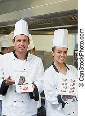 Two happy chefs presenting dessert plates