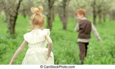 Two happy children boy and girl running around the flowering garden in slow motion