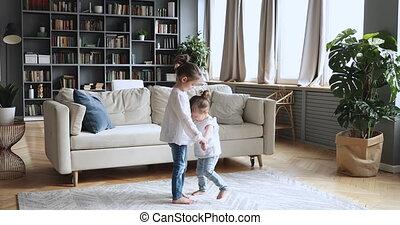 Two happy children girls holding hands dancing in living room