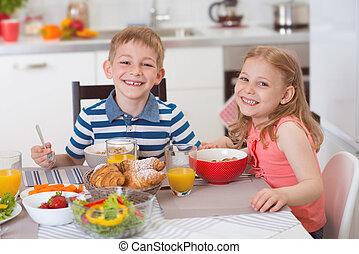 Two happy children having breakfast in kitchen