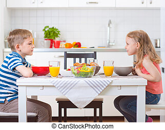 Two happy children having breakfast in kitchen