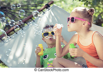 Two happy children lie on a hammock and play with soap bubbles