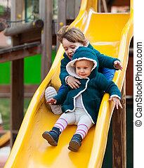 two happy children on slide