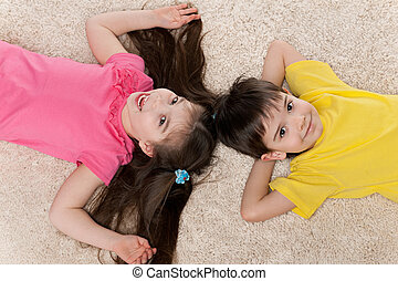 Two happy children on the white carpet