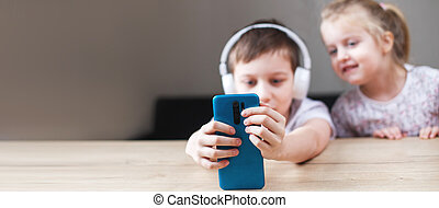 two happy children playing on the smartphone in headphones. people, children and technology concept. banner