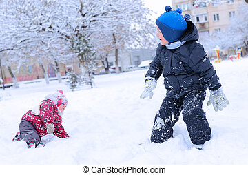 Two happy children playing snowball