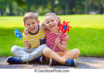 Two happy children playing with windmill