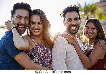 Two happy couples embracing together outside smiling