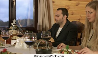 Two happy couples having dinner and clinking glasses with wine in a restaurant