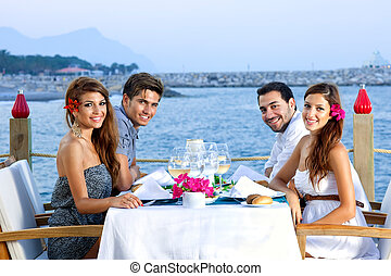 Two happy couples having dinner at the seaside - Two happy...