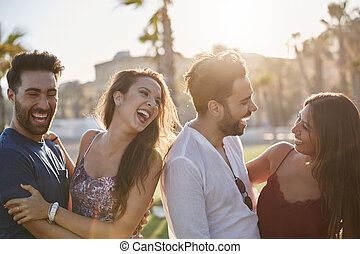 Two happy couples having fun outside laughing