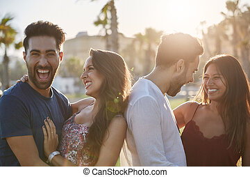 Two happy couples standing together outside laughing